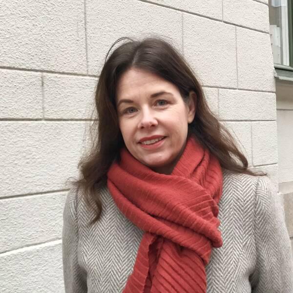 Christine Fransholm iklädd kappa och roströd halsduk står utomhus framför en husfasad.