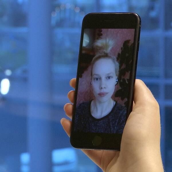 En kvinna med blont hår uppsatt i tofs syns på en mobilskärm. Hon har svart tröja och hörlurar i öronen.