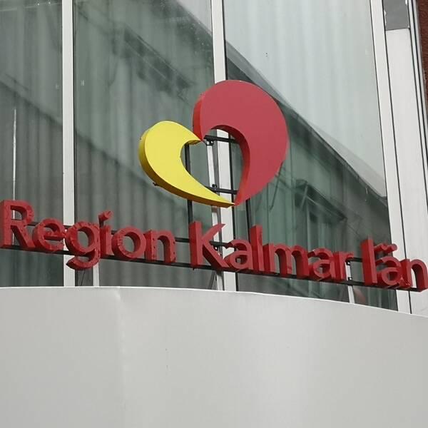 En bild på region Kalmar läns entréskylt utanför regionhuset. Det står Region Kalmar län med röda bokstäver och ovanför är deras logotyp. Ett hjärta i rött och gult.
