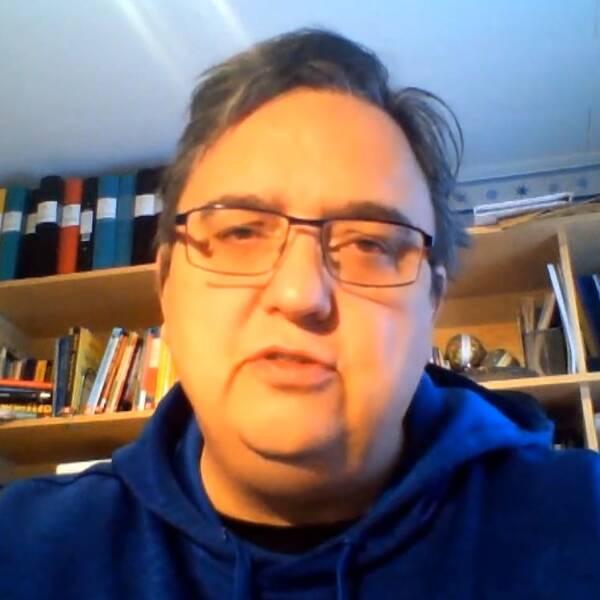 Man med kort mörkt hår, glasögon och blå hood-tröja sitter framför bokhyllor