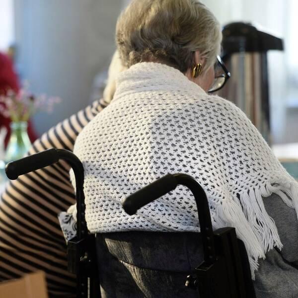 Bild på en äldre dam med sjal som sitter i en rullator vid ett bord.
