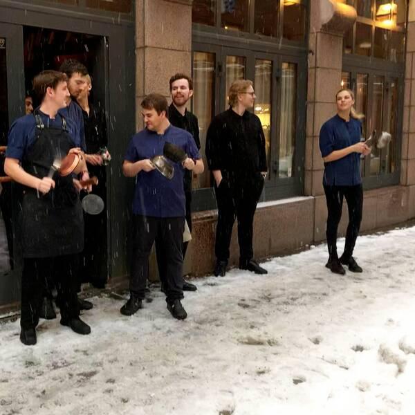 Personer i restaurangkläder som står på en gata och slår på kastruller.