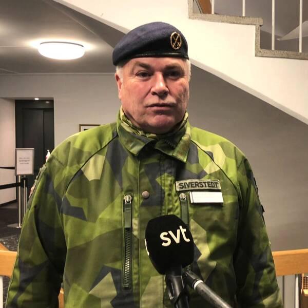 en medelålders man i militärens kamouflagekläder och basker intervjuas framför en trappa