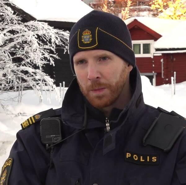 Manlig polis står i ett område med snö. Röda stugor i bakgrunden.