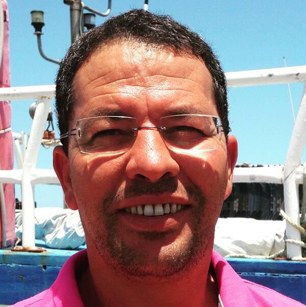 Fiskaren Chamseddine Bourassine har fängslats av i Italien, anklagad för människosmuggling. Han hävdar att han försökt att hjälpa migranter i sjönöd.