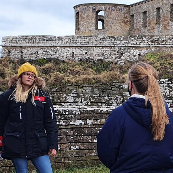 Bilden är ett collage. Den vänstra bilden föreställer två kvinnor som står framför slottsruinen i Borgholm. Den ena står till vänster i bild och tittar på kvinnan mittemot henne. Hon har gulmössa, blont hår, glasögon och en dunjacka med SVT:s logotyp på. Den andra kvinna står till höger i bilden och vi ser bara ryggen på henne. Hon syns från midjan och uppåt. Hon har ljusbrunt hår i en hästsvans och marinblå jacka. Vid sidan av hennes ansikte skymtar ett munskydd. Den högra bilden är en porträtt bild på tillförordnad socialchef i Borgholms kommun, Lars-Gunnar Fagerberg. Han syns från bröstet och uppåt. Han har marinblå finstickad tröja med en ljusblå skjorta under.