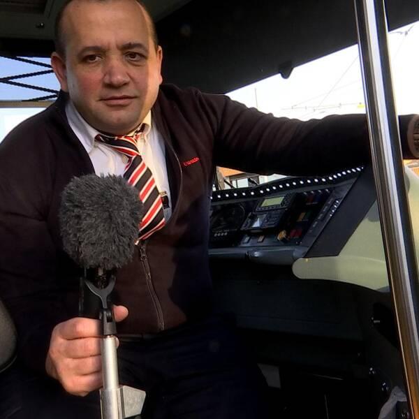 En spårvagnschaufför sitter i förarhytten och lutar sig mot mikrofonen.