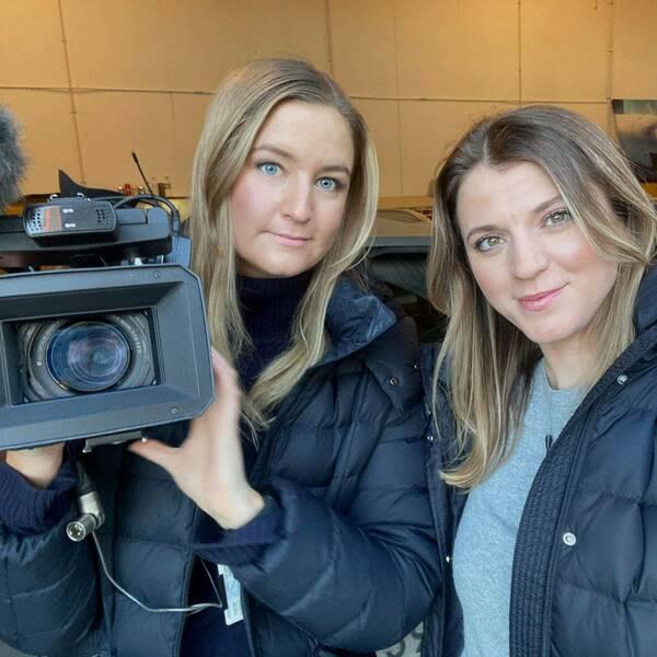 Två kvinnor med blondt hår och blåa jackor. I ena handen hålls en videokamera.