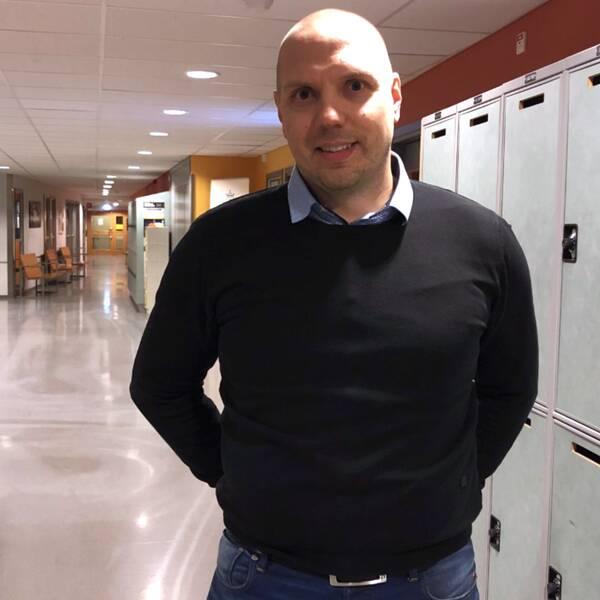 En man står i en skolkorridor med elevskåp runt omkring sig.