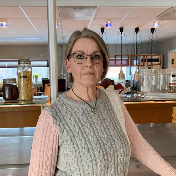 Eva-Marie Sedergren står i en restaurang bar som är stängd med buffé i bakgrunden.