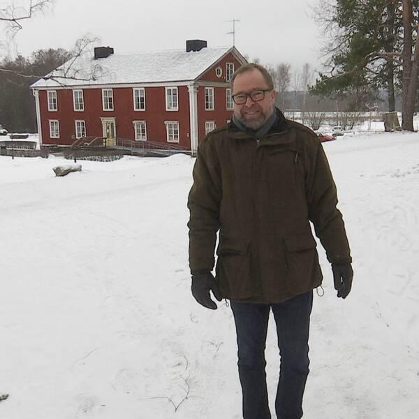Peter Sundell framför ett rött hus i parkmiljö.