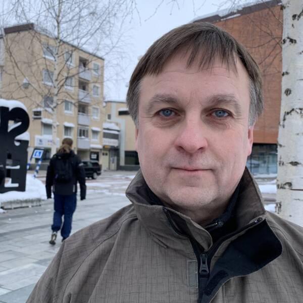 Socialdemokratiskt kommunalråd i Skellefteå, Lorents Burman, kollar in i kameralinsen. I bakgrunden syns baksidan av Skellefteå-bokstäverna på torget i centrum.