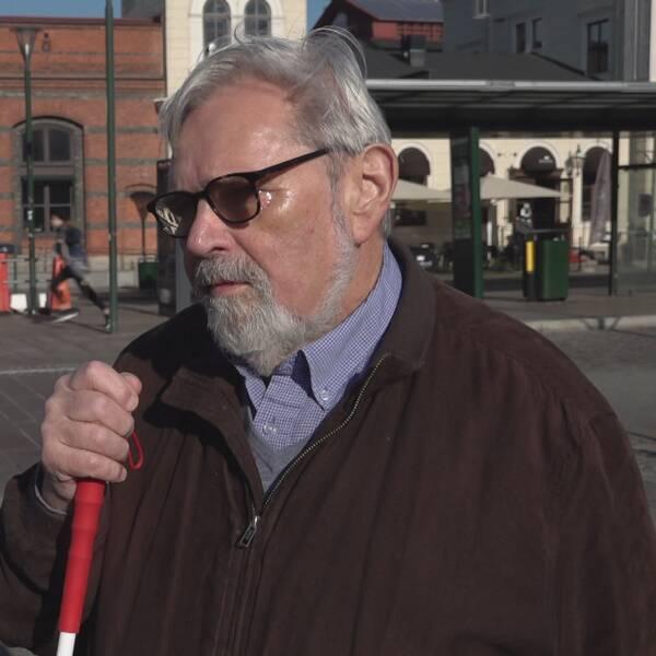 Blind man med glasögon och käpp framför centralstationen i Malmö.