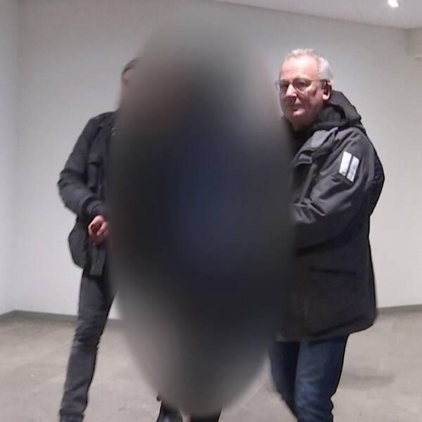 Man med polisuniform och armarna bakom ryggen. Bredvid två civilpoliser som