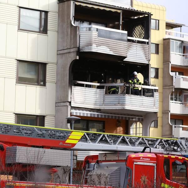 Brandmän på en balkong i ett lägenhetshus. Spår av brand på balkongen.