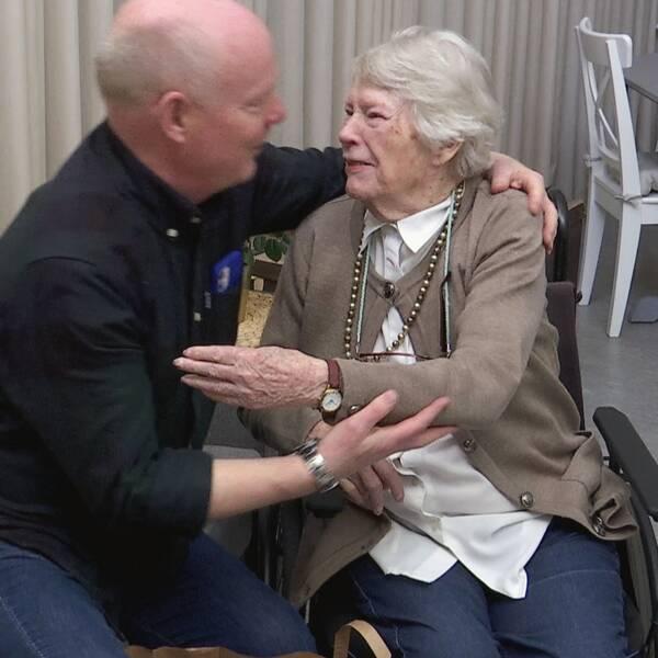Bilden visar hur en medelåldersman omfamnar en äldre kvinna.