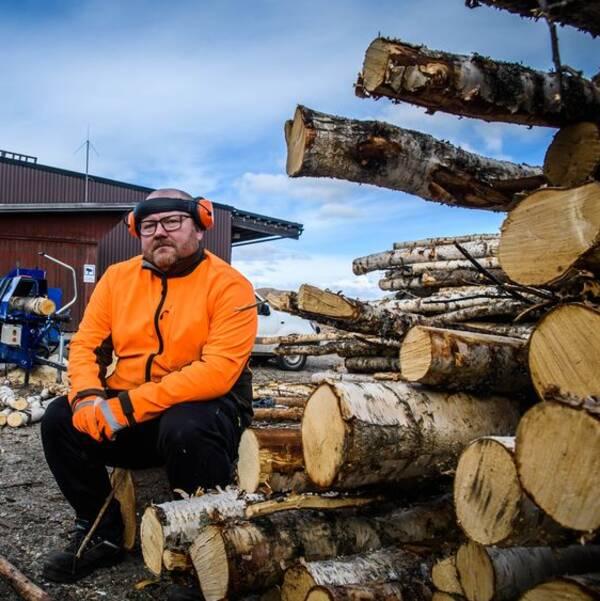 en man i varseljacka och hörselkåpor sitter vid en stapel björkstammar, vedkap och förrådslada i bakgrunden