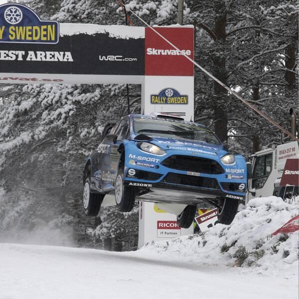 En blå bil flyger fram längs en snötäckt väg. En man med skjorta och rock.