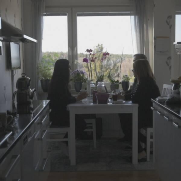 Tre personer sitter vid ett matbord i ett kök.