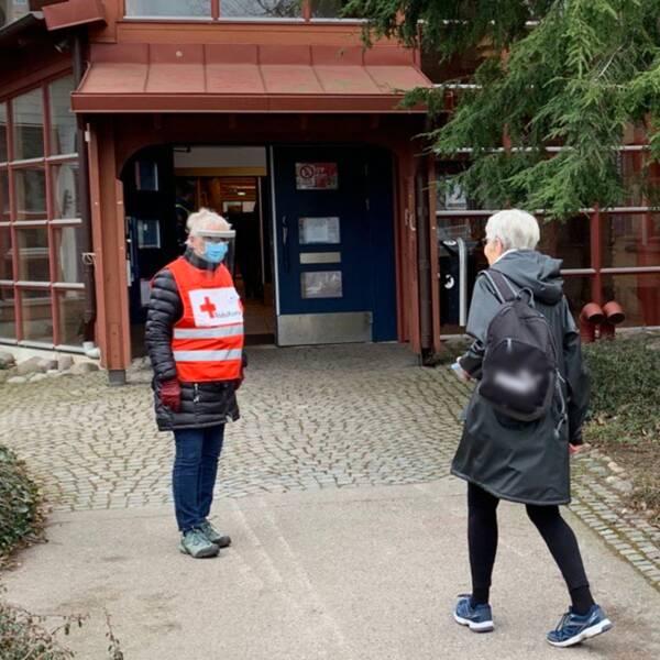 En äldre kvinna är på väg in i Kalmars vaccinationscentral. Utanför möts hon av en annan kvinna som arbetar som funktionär. Hon har skyddsutrustning och reflexväst.
