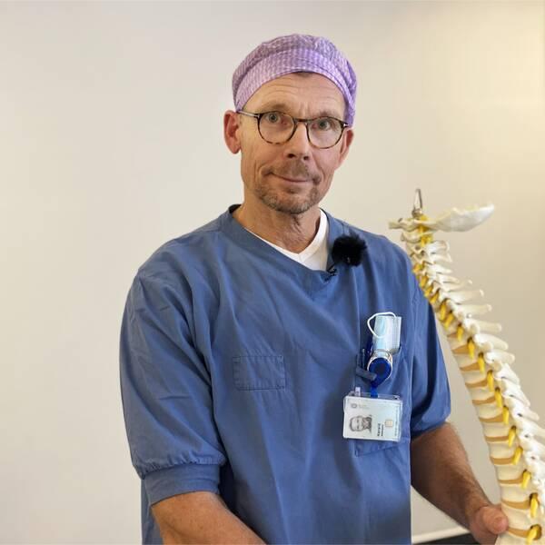 Harald Zetterquist i blå sjukhusklädsel står bredvid en modell av en ryggrad.
