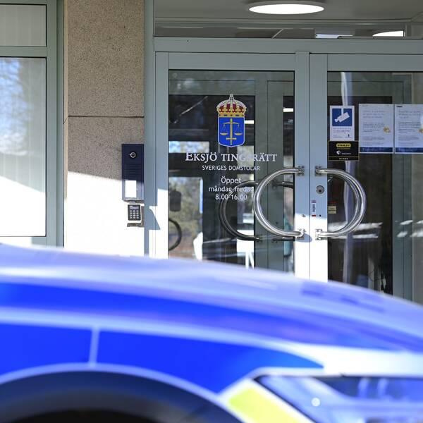 En polisbil står parkerad utanför byggnaden där Eksjö tingsrätt har sina lokaler.