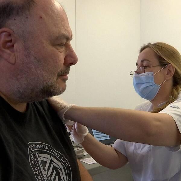 Levent får en spruta i armen av sjuksköterskan som bär munskydd