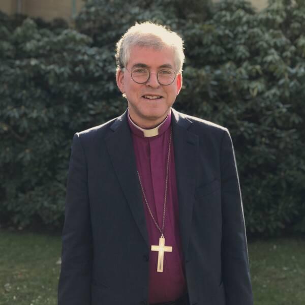 Biskop Åke Bonnier i kavaj framför gröna växter