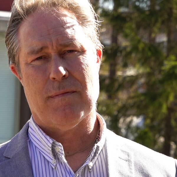 Ronny Lestander står utomhus i solsken och kollar in i kameran, bakom syns lite husfasad och några granar.