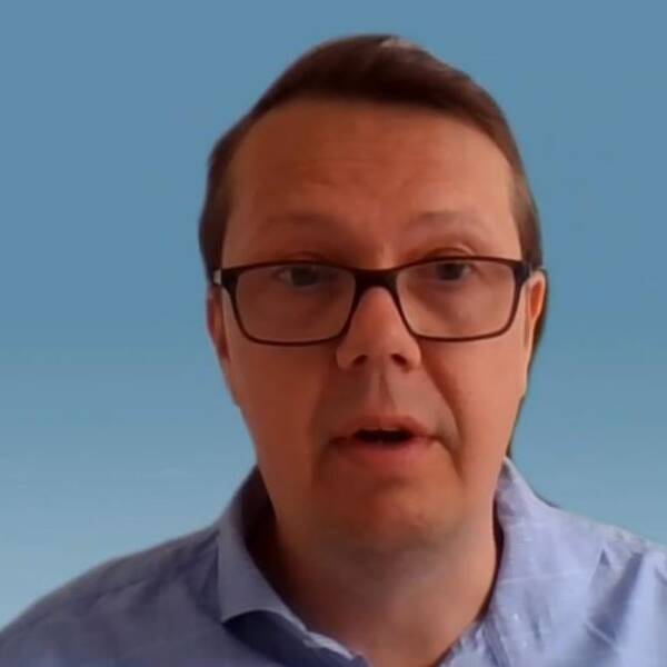 Man med glasögon och skjorta framför ljusblå bakgrund.
