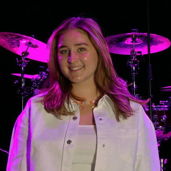 Paulina Johnson framför trumset belyst med lila ljus