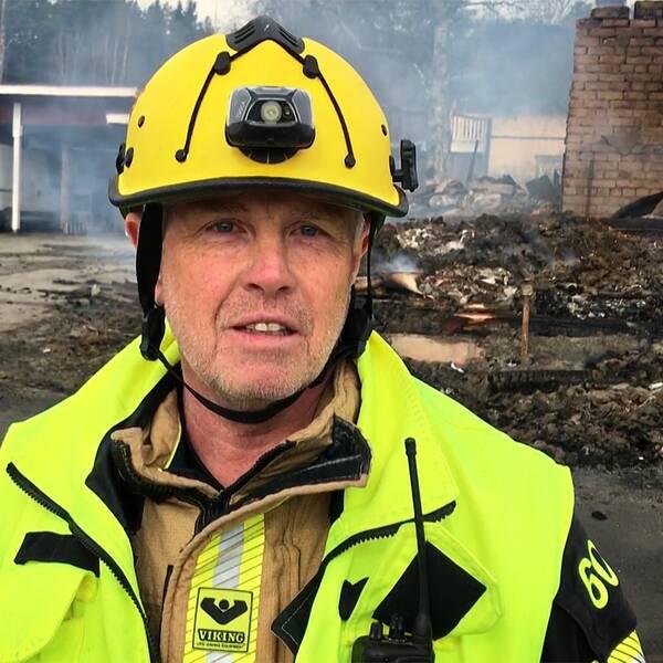 En man i gul hjälm och med varselkläder. I bakgrunden ser man bråte som brinner.