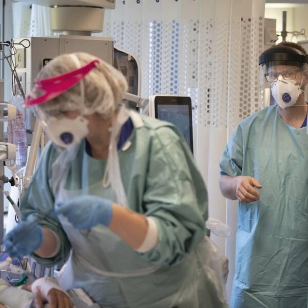 tre personer i skyddsutrustning på vårdavdelning