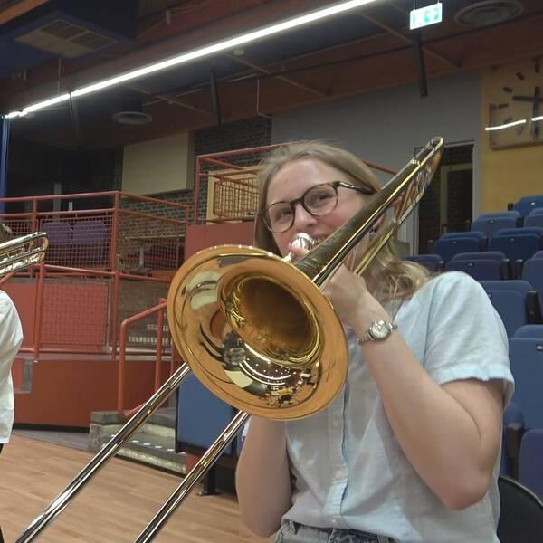 Glad tjej med trombon i stor sal.