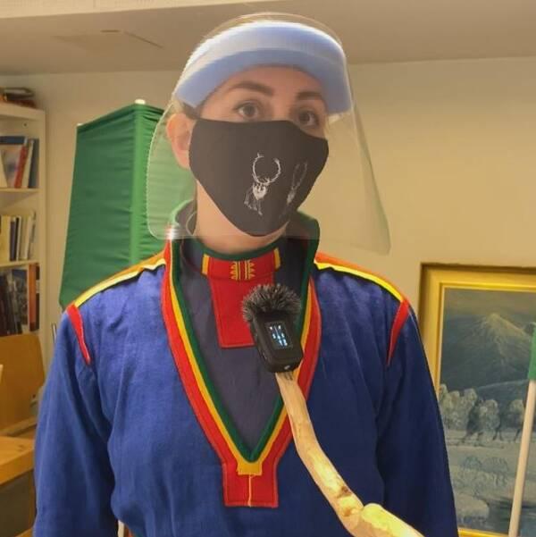 Kvinna i samisk klädnad och skyddsutrustning i form av munskydd och skärm.