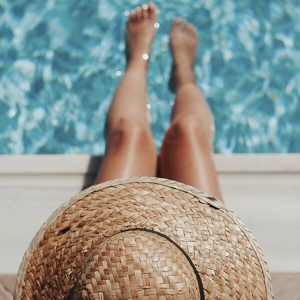 Person med solhatt sitter med fötterna i en pool, hudspecialisten Virginia Zazo och läkaren Karin Granberg.