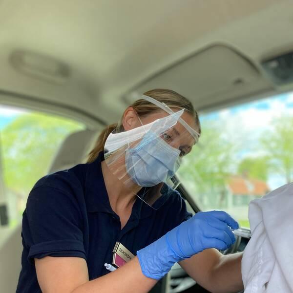 En sjuksköterska med munskydd, visir och blå plasthandskar vaccinerar en kvinna i pensionsåldern.