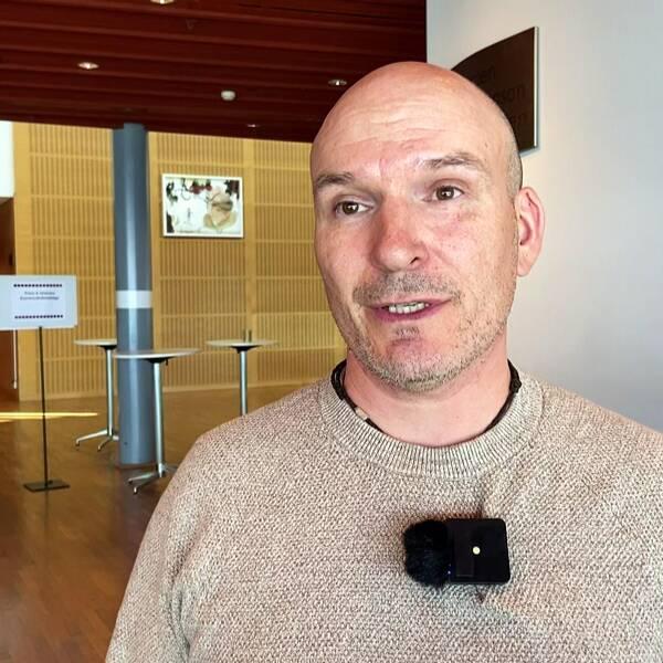en man som intervjuas i en större korridor