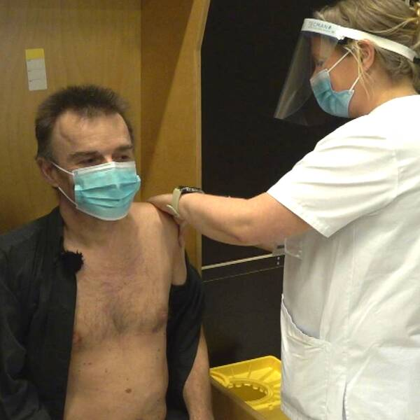 En man till vänster i bild går runt i stora lokaler och mannen i höger till bild blir vaccinerad.