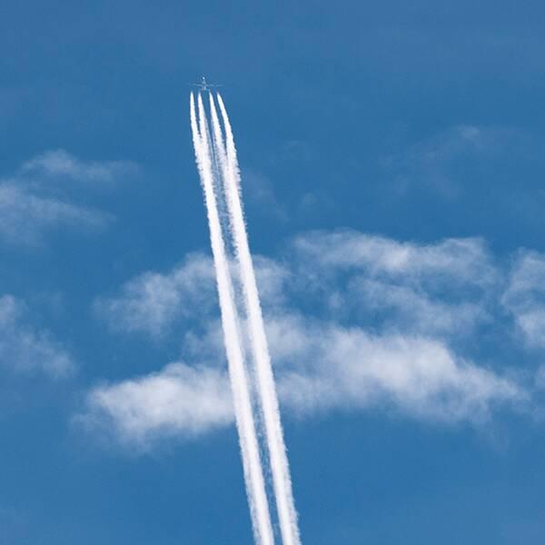 Kondensstrimmor efter flygplan/flygplan på landningsbana.