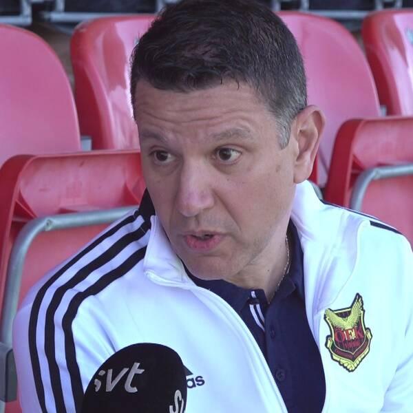 Man med mörkt kort hår och vit tröja sitter på en tom fotbollsläktare.