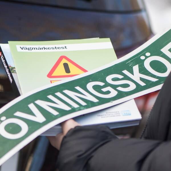 Övningskörsskylt på bil och kvinna med mörkt hår och glasögon.