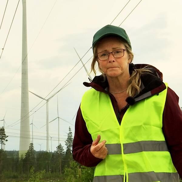 En kvinna i gul varselväst med vindkraftverk i bakgrunden.