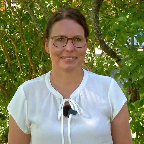 Jenny Höckert framför grönskande buskage