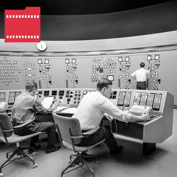 Svartvit bild där män sitter framför monitorer.