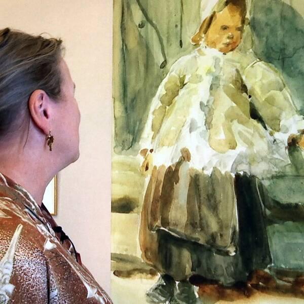 kvinna ses snett bakirån, tittar på akvarellmålning av ett barn