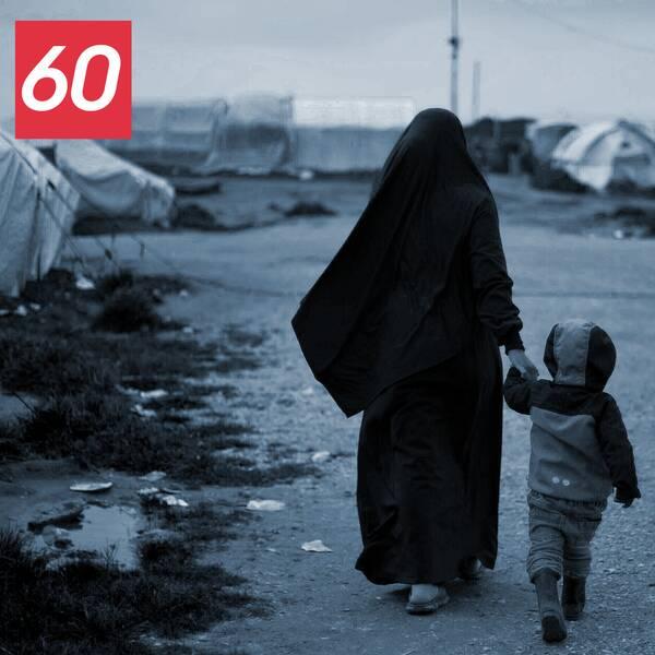 Kvinna i burka håller barn i handen på ett läger i nordöstra Syrien.