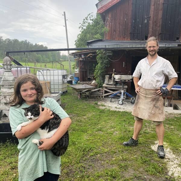 Flicka med katt, Philipp Rose framför sin verkstad i regnet.