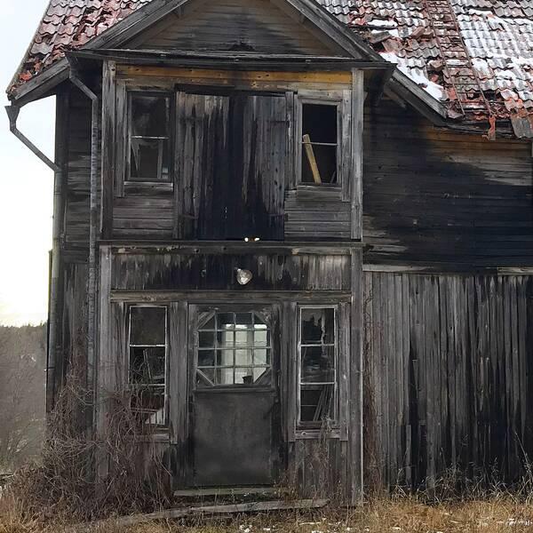 Gammalt ödehus utan färg på fasaden och tegelpannor har rasat från taket.