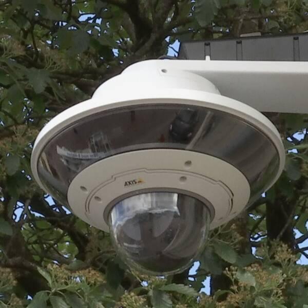 Övervakningskamera delat med man i skjorta och glasögon
